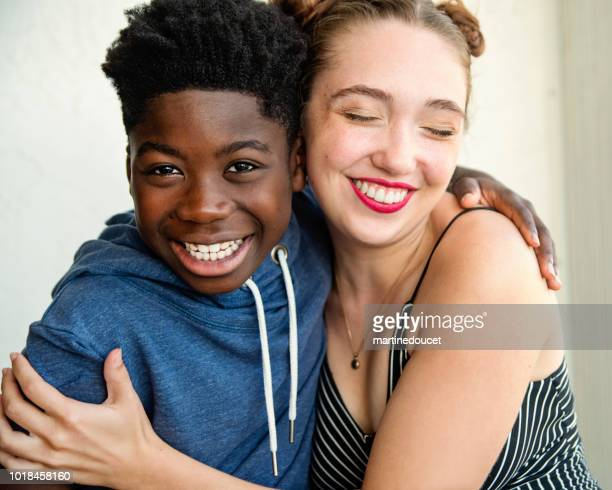Young caucasian woman and african-american boy portrait.