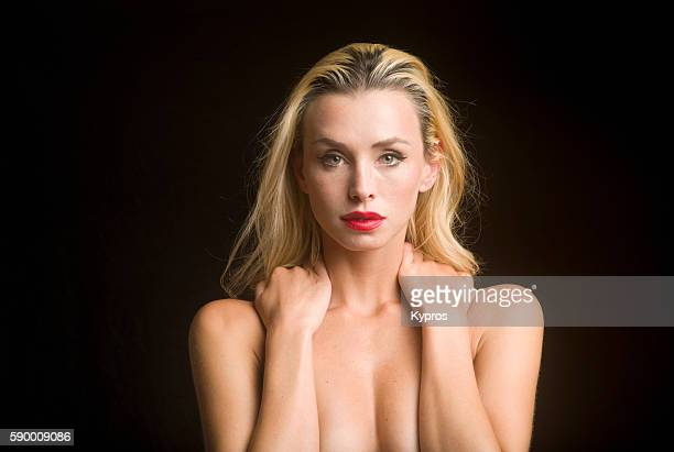 young caucasian woman covering her chest with her arms, close up, studio shot - risque woman stock photos and pictures