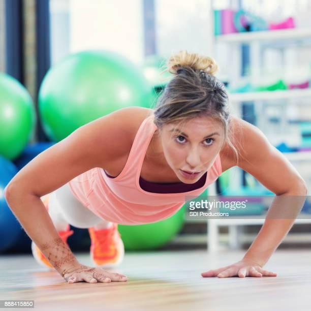 Mujer joven caucásica haciendo push ups en health club