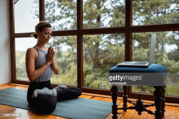 young caucasian woman exercising at home - mid adult stock pictures, royalty-free photos & images