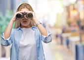 young caucasian woman holding binoculars over