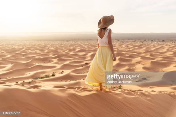 a young caucasian woman in a long skirt, shirt and straw hat standing on top of a sand dune and looks towards the sunrise. sunrise in the merzouga (sahara) desert. - skirt stock pictures, royalty-free photos & images