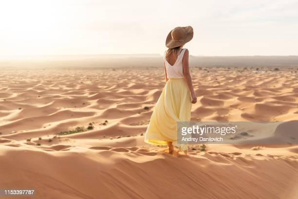 een jonge kaukasische vrouw in een lange rok, hemd en strohoed staande op de top van een zandduin en kijkt naar de zonsopgang. zonsopgang in de merzouga (sahara) woestijn. - rok stockfoto's en -beelden