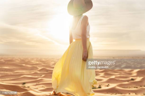 a young caucasian woman in a long skirt, shirt and straw hat standing on top of a sand dune and looks towards the sunrise. sunrise in the merzouga (sahara) desert. - ankle length stock pictures, royalty-free photos & images