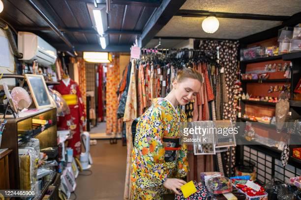 young caucasian woman in kimono shopping in japanese kimono store - obi sash stock pictures, royalty-free photos & images