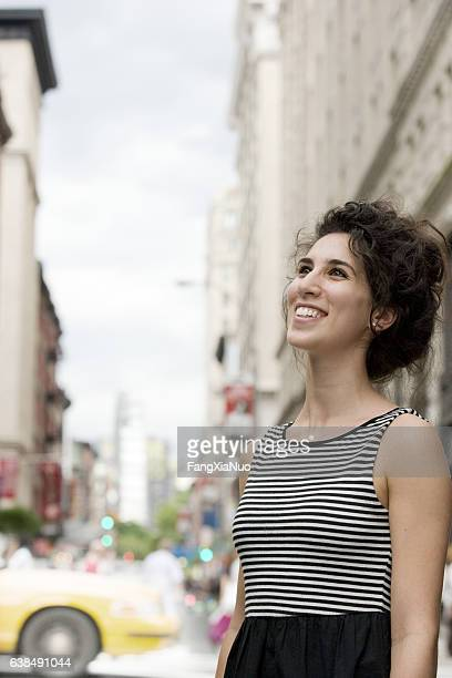young caucasian woman looking upward in downtown city - new yorker building stock photos and pictures