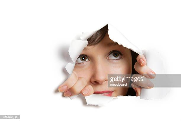 young caucasian woman peeking from ripped paper hole - peeping holes ストックフォトと画像