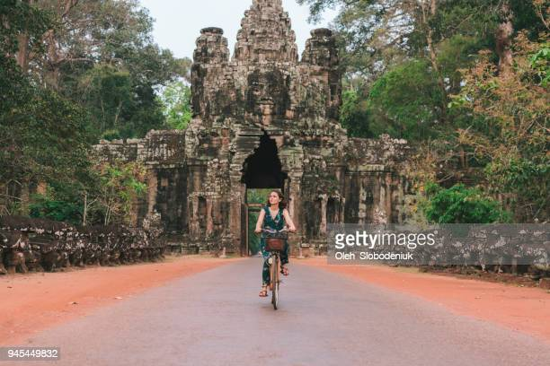 young caucasian woman riding  bicycle  in angkor wat - angkor wat stock pictures, royalty-free photos & images