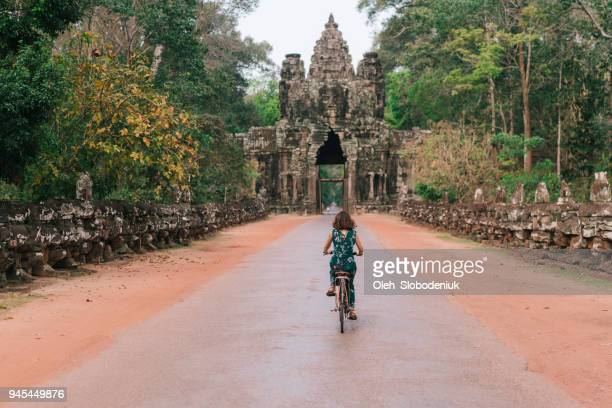 young caucasian woman riding  bicycle  in angkor wat - cambodia stock pictures, royalty-free photos & images