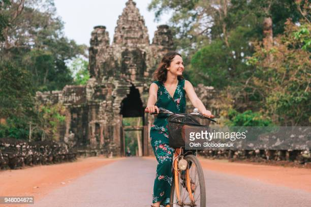 young caucasian woman riding  bicycle  in angkor wat - angkor stock photos and pictures