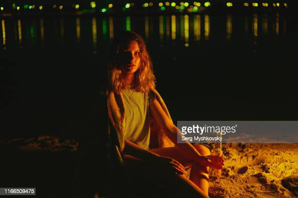 young caucasian woman sitting near a bonfire with a glass bottle at night - myshkovsky stock photos and pictures