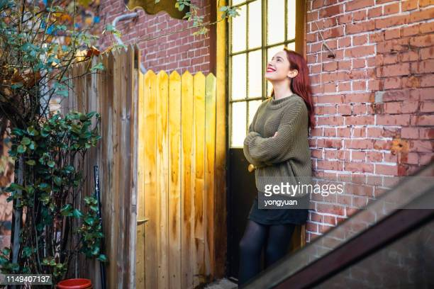 young caucasian woman standing beside a door - one young woman only stock pictures, royalty-free photos & images