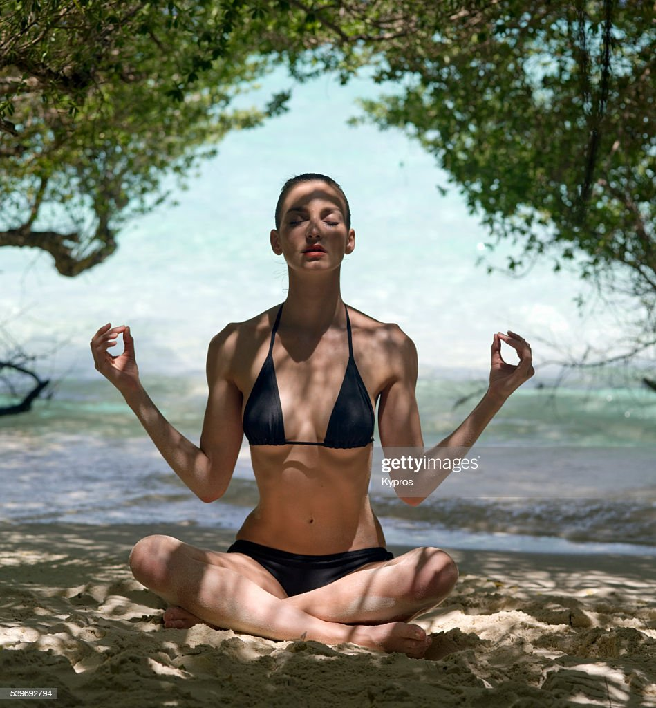 Young Caucasian Woman Wearing Bikini At The Beach Meditating - Maldives : Stock Photo