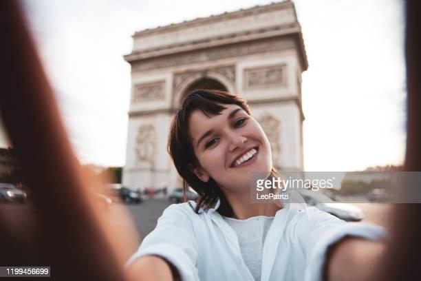 市内中心部のパリを歩く若い白人女性は、市内のランドマーク、トゥール・エッフェル、凱旋門を探索しながら、電話や通勤で話したり、テキストメッセージを送り合っています。 - パリ凱旋門 ストックフォトと画像