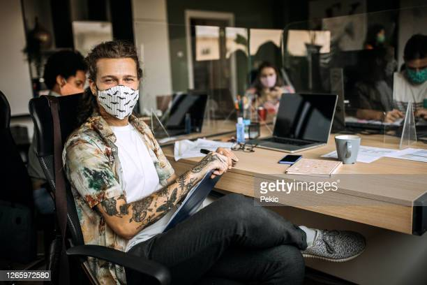 young causally clothed businessman posing for a photo with a face mask - avoidance stock pictures, royalty-free photos & images