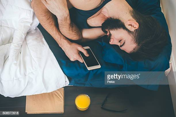 Young cell phone addict man sleeping and holding it