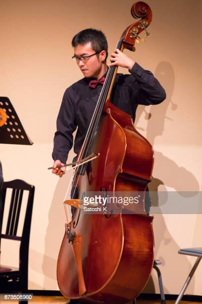 young cellist playing cello on stage - violin family stock photos and pictures