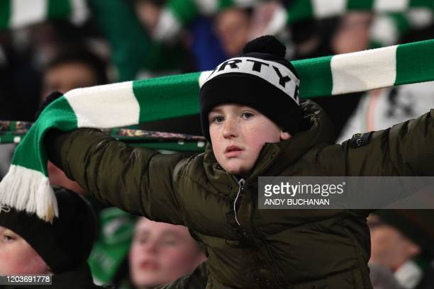 A young Celtic supporter holds up his scarf in the crowd before kick off in the UEFA Europa League round of 32 second leg football match between...