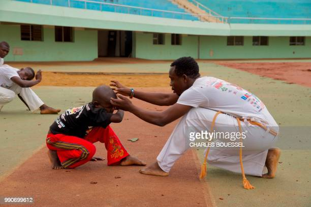 A young Central African 'Capoeirista' plays a game of Capoeira during a training session at the stadium in Bangui on July 1 2018 Every Sunday young...