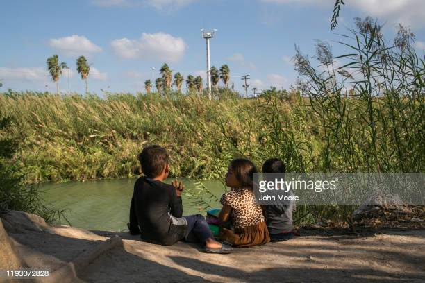Young Central American asylum seekers sit on the bank of the Rio Grand at a camp for asylum seekers as cameras from American surveillance tower look...