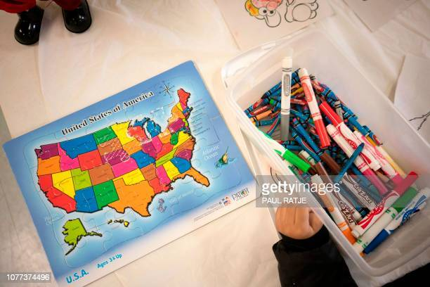 A young Central American child colors next to a puzzle of the United States inside the church hall of the Basilica of San Albino in Mesilla New...