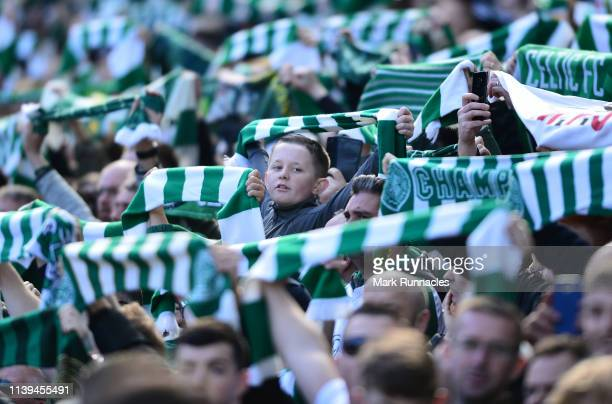 A young Cetlic fan looks through the Scarfs being held up by Celtic fans during the Ladbrokes Scottish Premiership match between Celtic and Rangers...