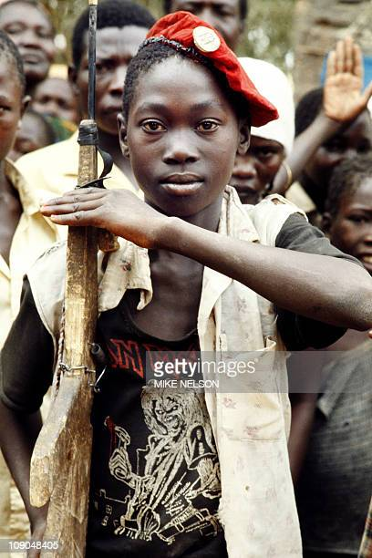 Young Chadian boy scout salutes, holding a wooden rifle, on February 23 in Doba during the Chadian-Libyan conflict.