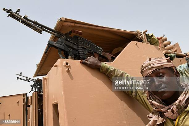 A young Chadian soldier poses next an armoured vehicle near Malam Fatori on April 3 after the town in northeastern Nigeria was retaken from Boko...