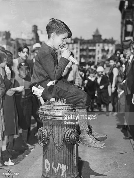Young Charles Frankel sits on a fire hydrant and eats a candy bar in front of a crowd of onlookers.