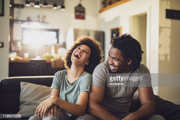 young cheerful african american couple in the living room. - coppia di giovani foto e immagini stock
