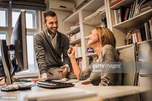 young cheerful business colleagues flirting at corporate office. - work romance stock pictures, royalty-free photos & images
