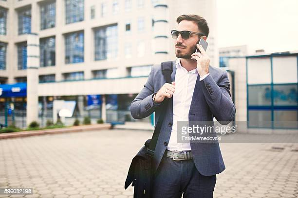young cheerful businessman using mobile phone outdoors. - shoulder bag stock pictures, royalty-free photos & images