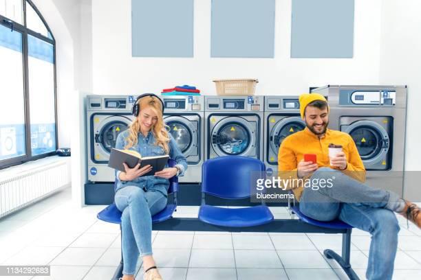 junges, fröhliches paar, das im waschsalon gemeinsam wäsche spült. - waschsalon stock-fotos und bilder