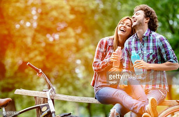 Young Cheerful Couple Drinking Water After Riding Bicycles.