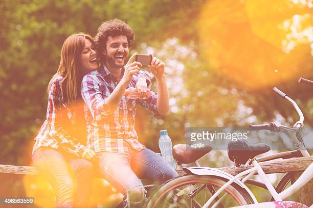 Young Cheerful Couple Drinking Water And Looking at Smart Phone.