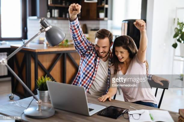 junges fröhliches paar genießt den kauf von online-aktien - rechnen stock-fotos und bilder
