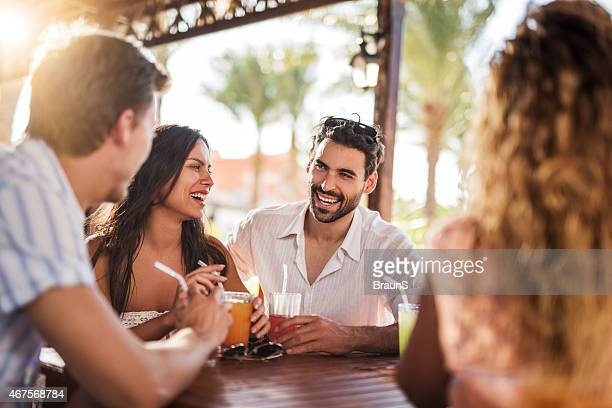 Young cheerful couple having fun with their friends in bar.
