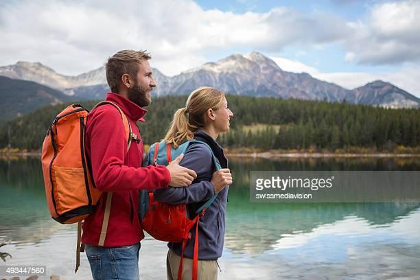 若い楽しいカップルのハイキング、湖の秋
