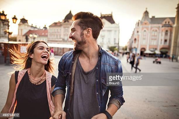 Junge fröhlich paar Laufen auf der Straße und viel miteinander lachen.