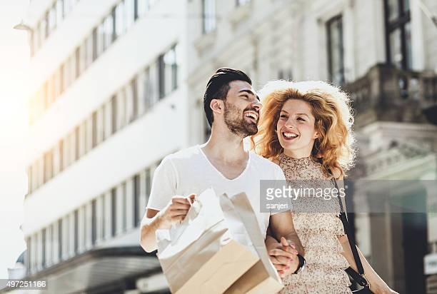 Young cheerful couple shopping and walking by the street