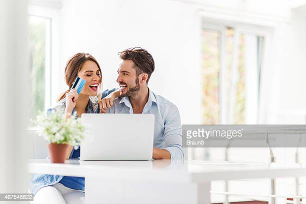 Young cheerful couple shopping online at home.