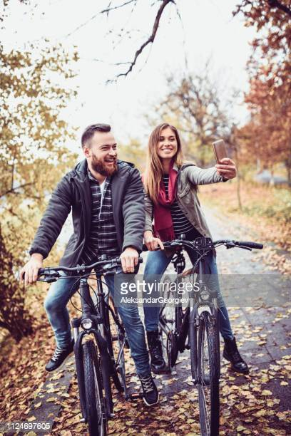 young cheerful couple taking a selfie while riding a bike - yellow coat stock pictures, royalty-free photos & images