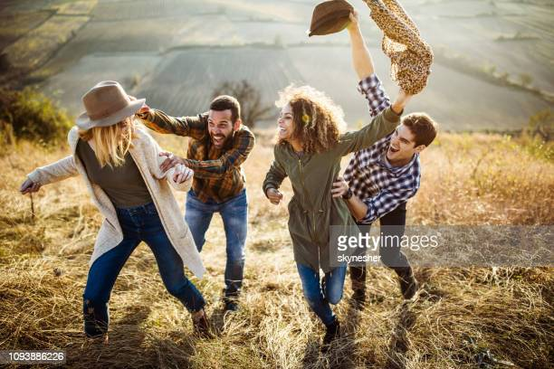 young cheerful couples chasing up the hill in autumn day. - homem pegando mulher imagens e fotografias de stock