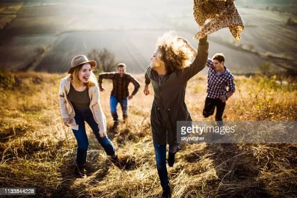 秋の日に丘を駆け上がる若い陽気カップル。 - つかまえる ストックフォトと画像