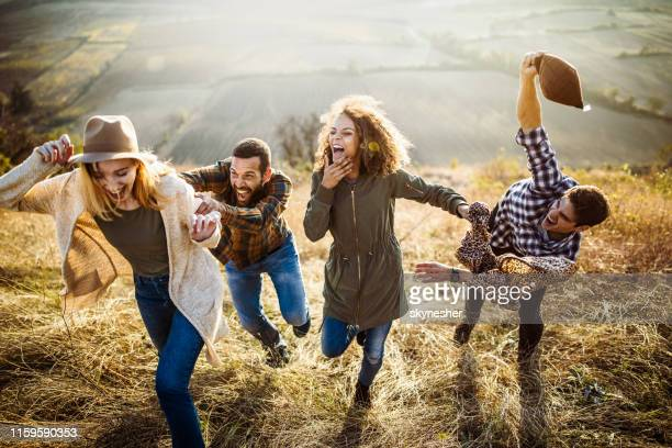 young cheerful couples chasing up the hill in autumn day. - chasing stock pictures, royalty-free photos & images
