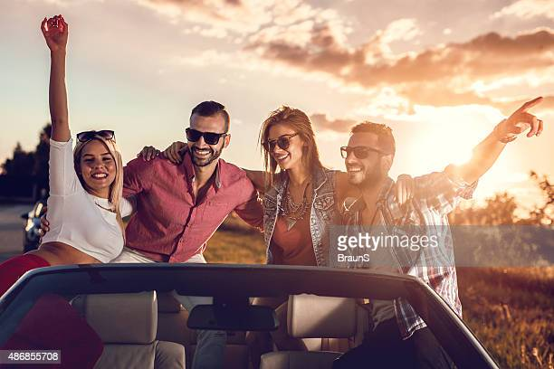Young cheerful couples having fun in cabriolet at sunset.