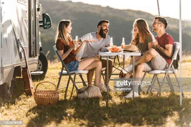 young cheerful couples talking at picnic table by the camp trailer. - camper van stock pictures, royalty-free photos & images