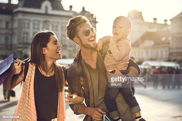 Young cheerful family enjoying in shopping day at the city.
