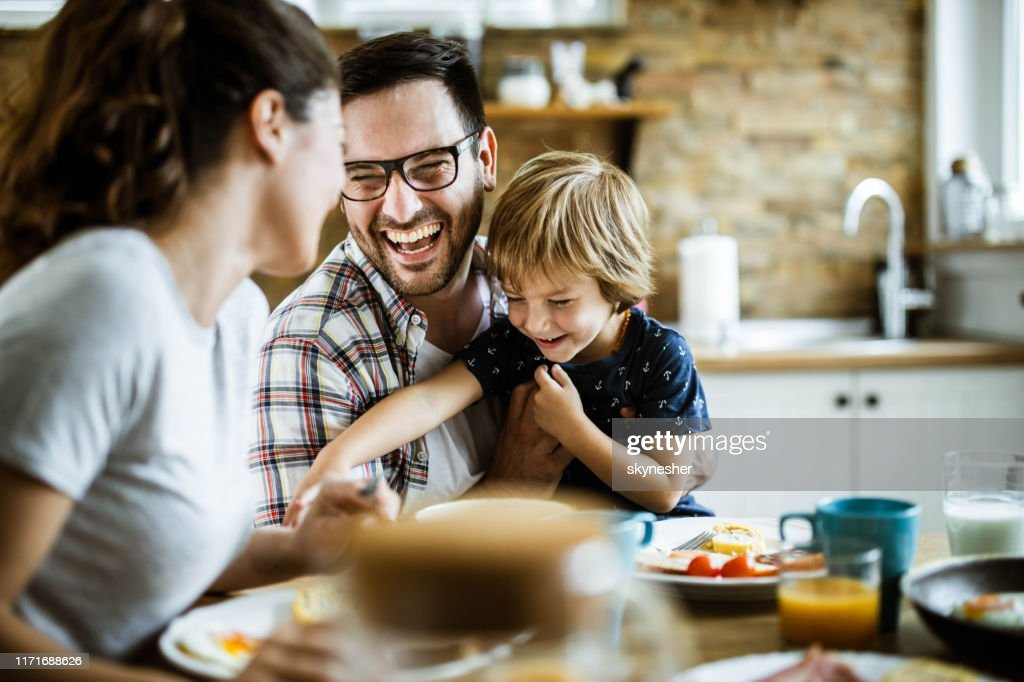 Young cheerful family having fun at dining table. : Stock Photo