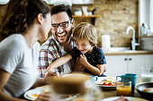 Young cheerful family having fun at dining table.